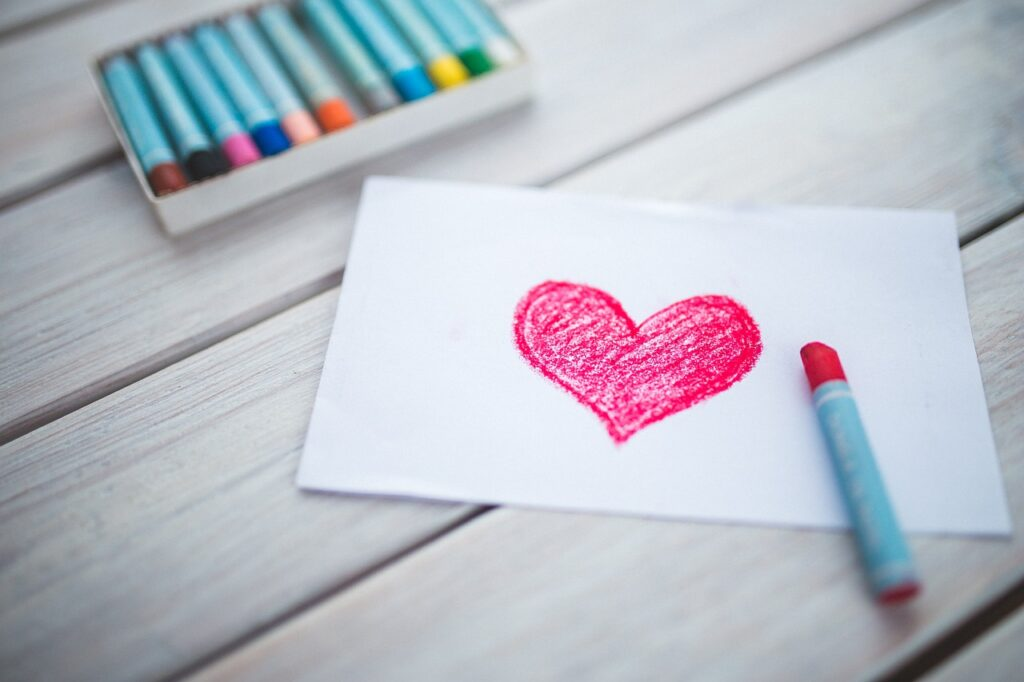 a heart drawing with pastel crayons next to it