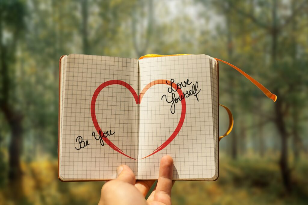 heart drawing in a book with hands holding