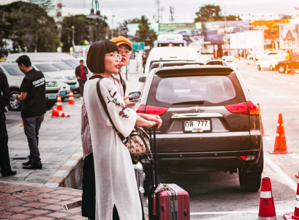 Women standing with suitcases near a parked car