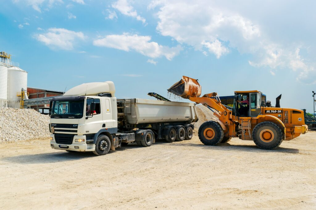 A brown loader beside a white cargo truck signifying movers that you can hire after you've found a real estate agent.
