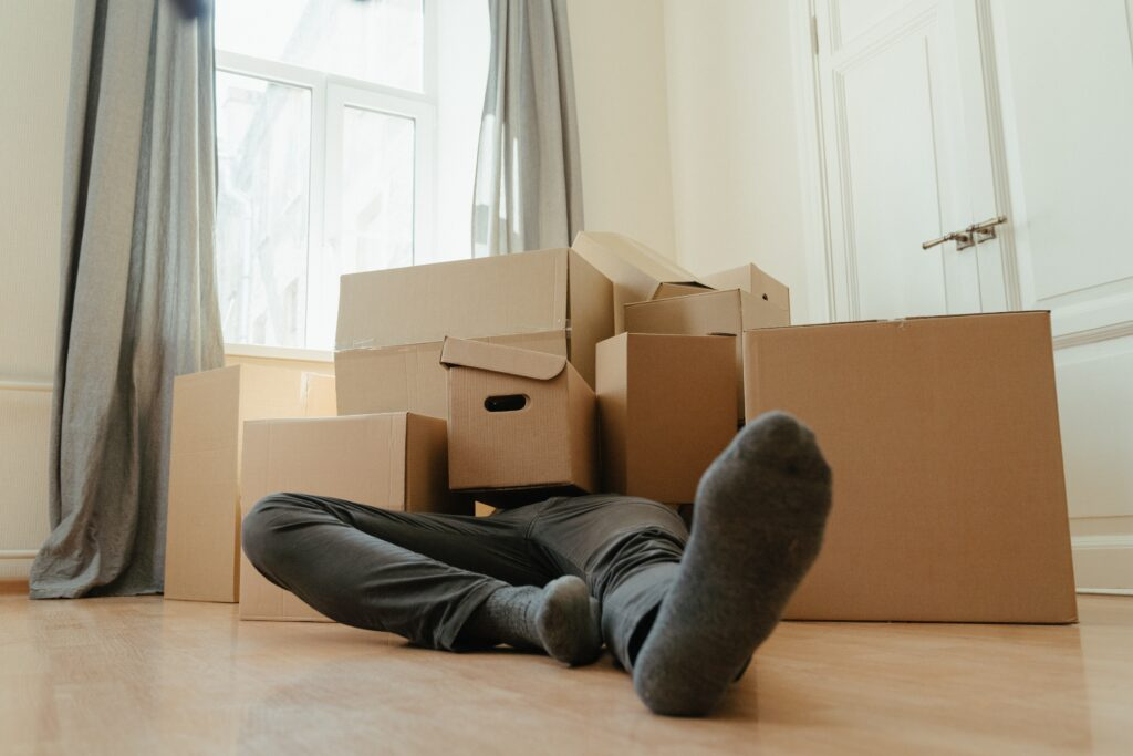 A man with sitting on a brown cardboard boxes