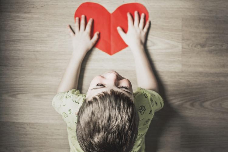 A cute little boy touching a paper heart.