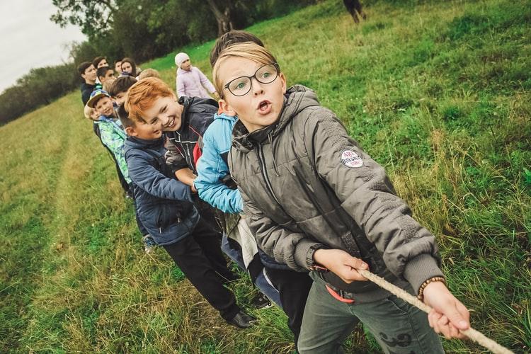 Kids playing tug of war in nature.