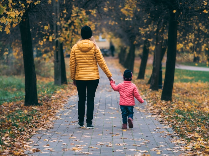 A mom enjoying her favorite fun exercise - walking with her little one.