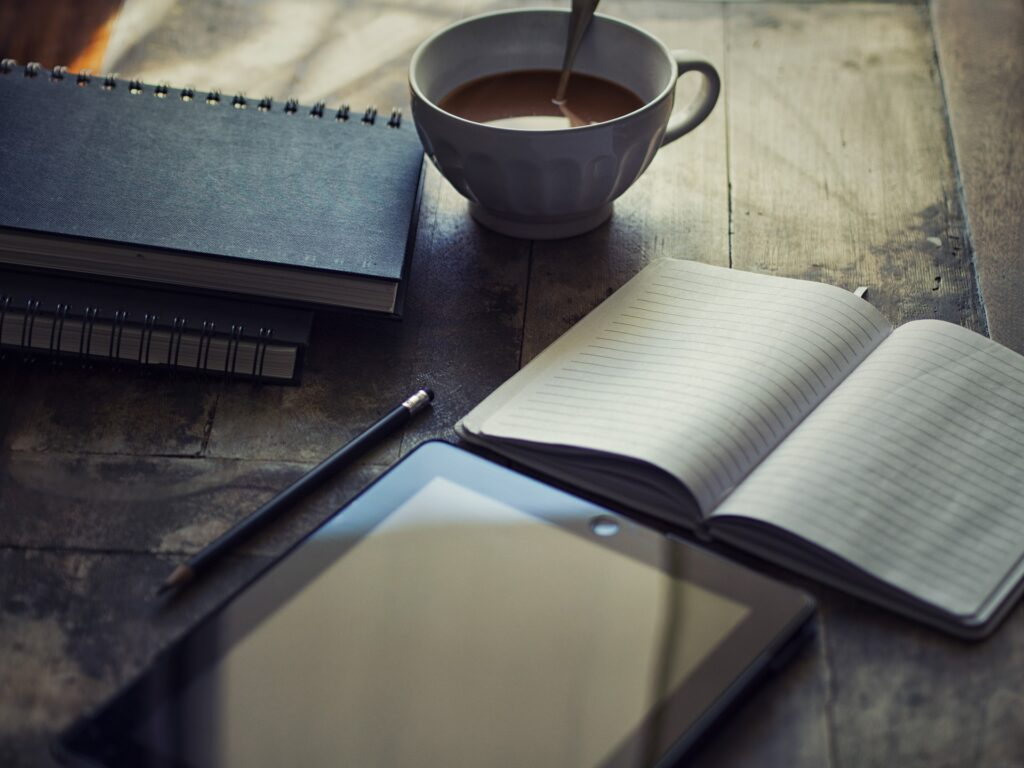 blogger work with book ad notebooks with a cup of coffee
