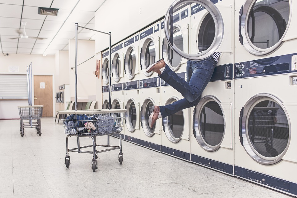 legs hanging out of a drier in a laundry mat.