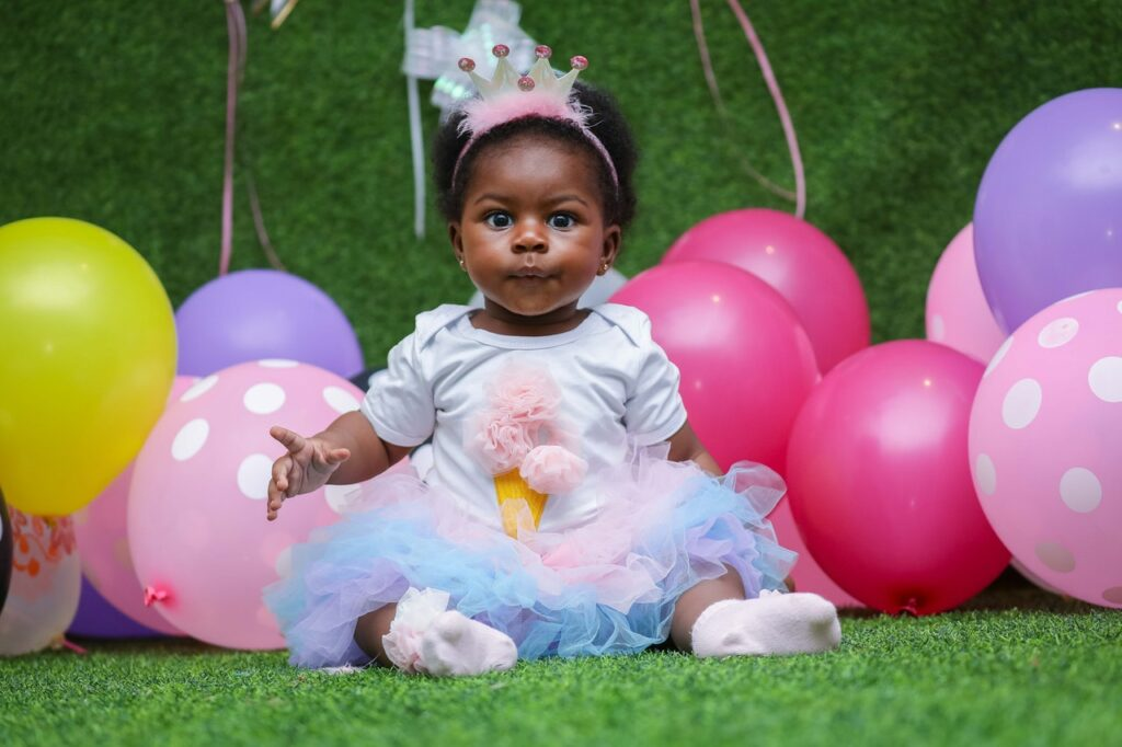 A baby girl celebrating her birthday in a birthday gown