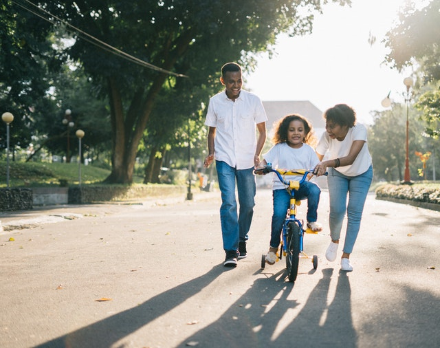 Parents teaching a girl to ride a bike.