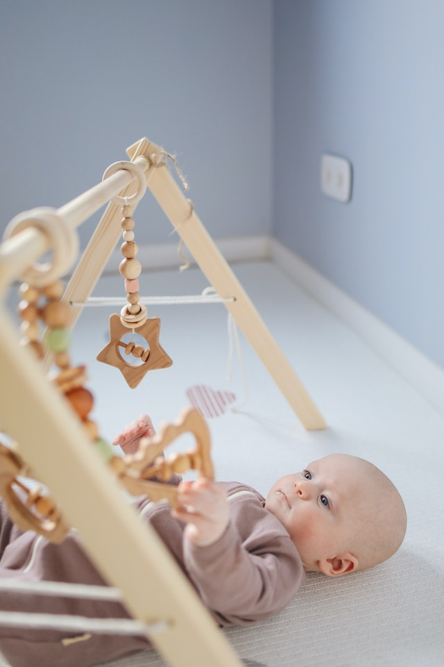 Baby playing with a wooden rattle