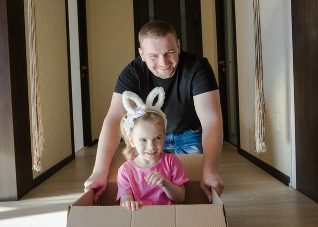 a man with a child in a cardboard box.
