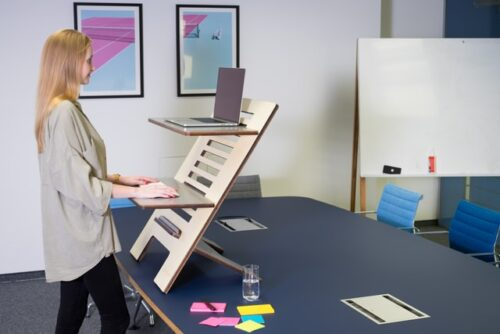 A woman following office space design trends and working on a standing desk.