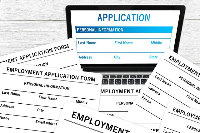Multiple application forms and a laptop showing application form on a website