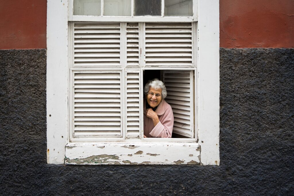Old lady on the window of a house