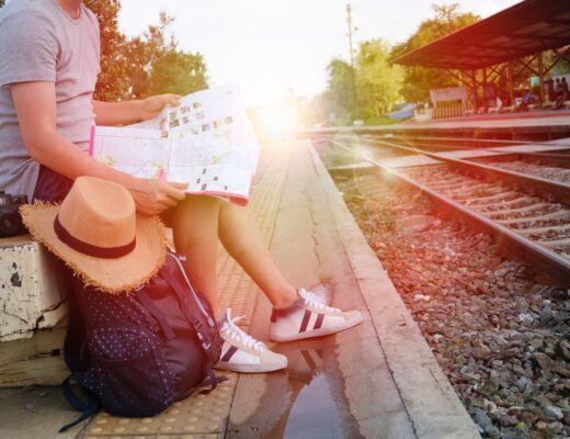 Backpack and traveler sitting near rails