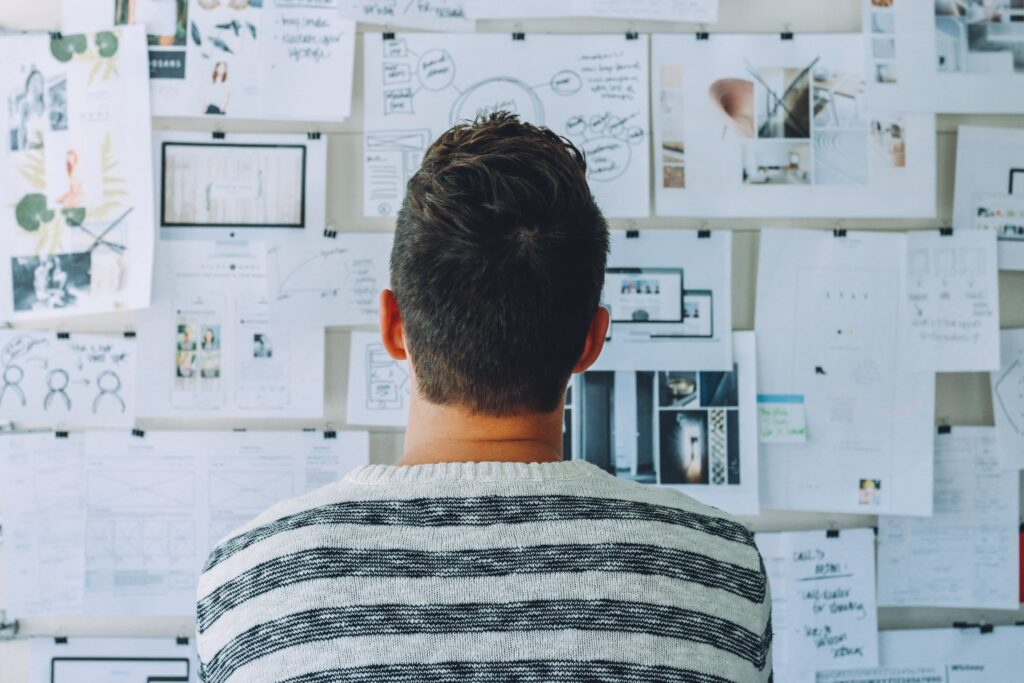 man looking at white board with post its