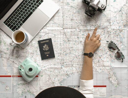 map passport camera laptop macbookpro glasses girl pointing