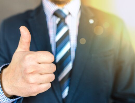 A real estate agent in a suit doing thumbs up. It's hard to find a real estate agent that's good.