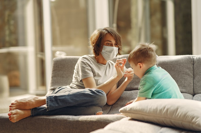 Mom wearing a face mask and playing with her son on a sofa