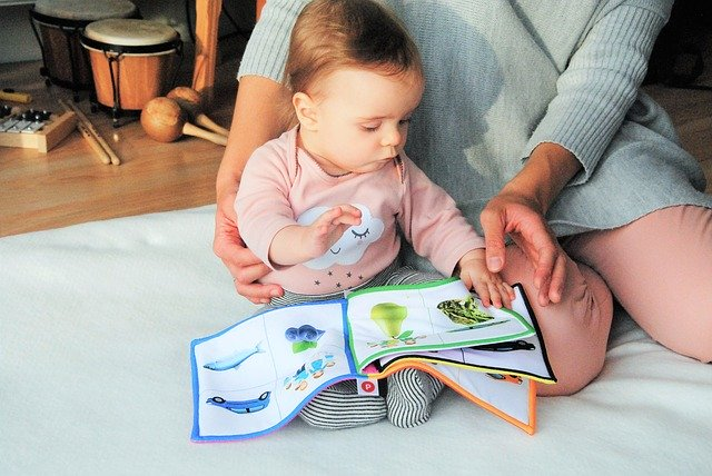 Mother and her baby playing with a soft book