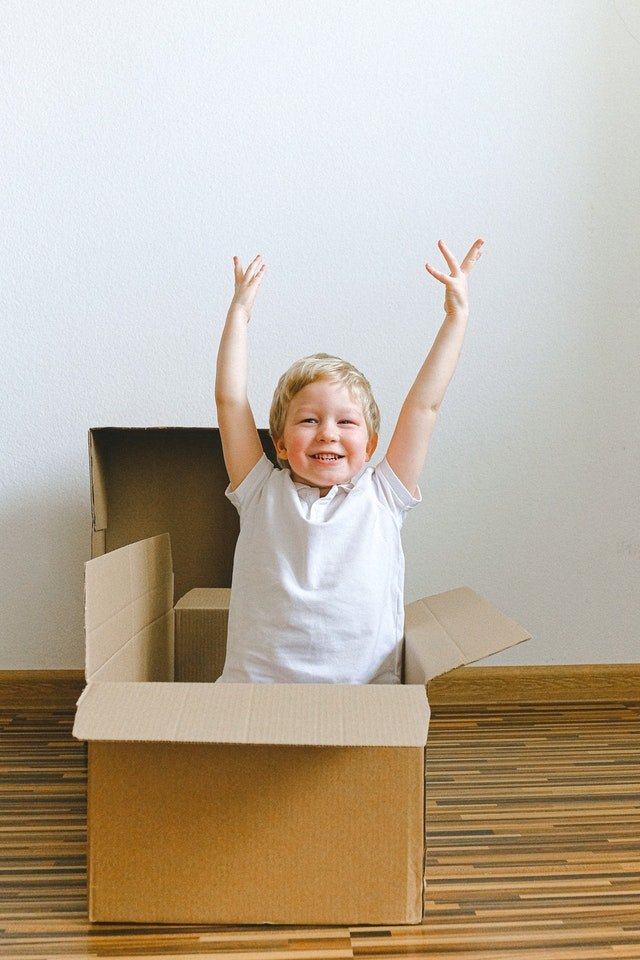 A boy playing with empty moving boxes to illustrate that such simple things can keep kids entertained during lockdown