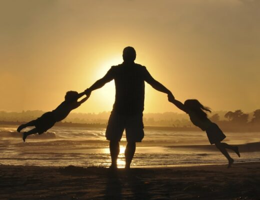 A dad playing on the beach with his kids during a gorgeous sunset.