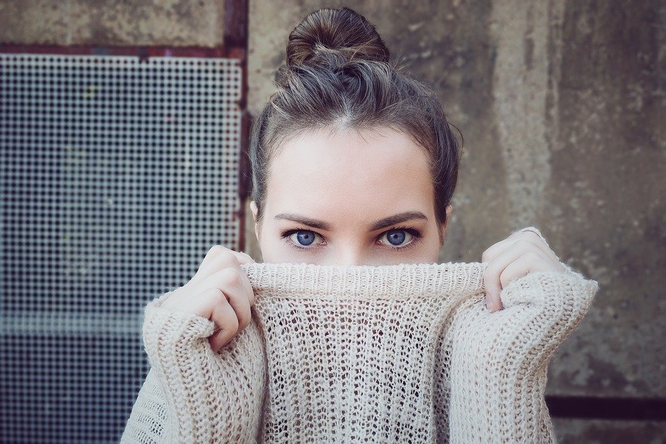 a girl in a sweater that was stored during the summertime.