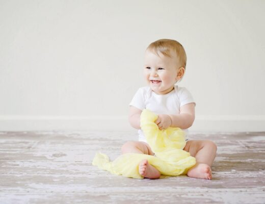 A baby holding a toy and smiling