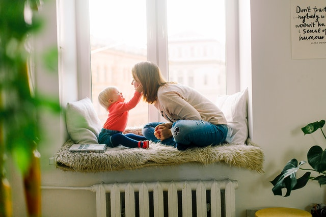 A woman and a baby sitting by a window.