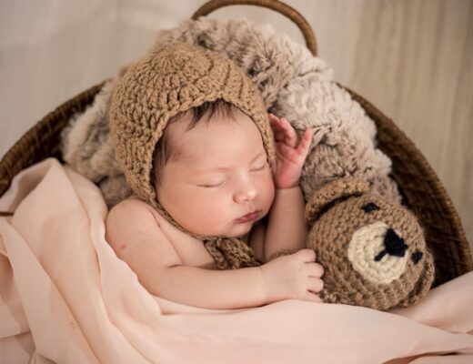 A baby wearing a brown knit cap while sleeping