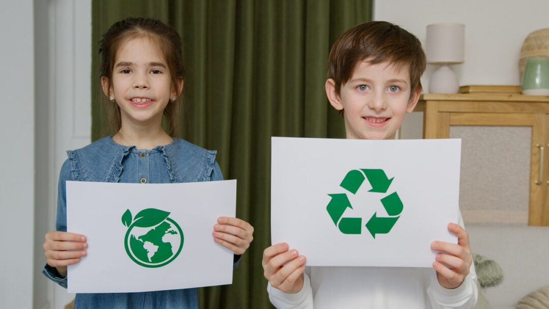 Two kids holding papers with recycling symbols