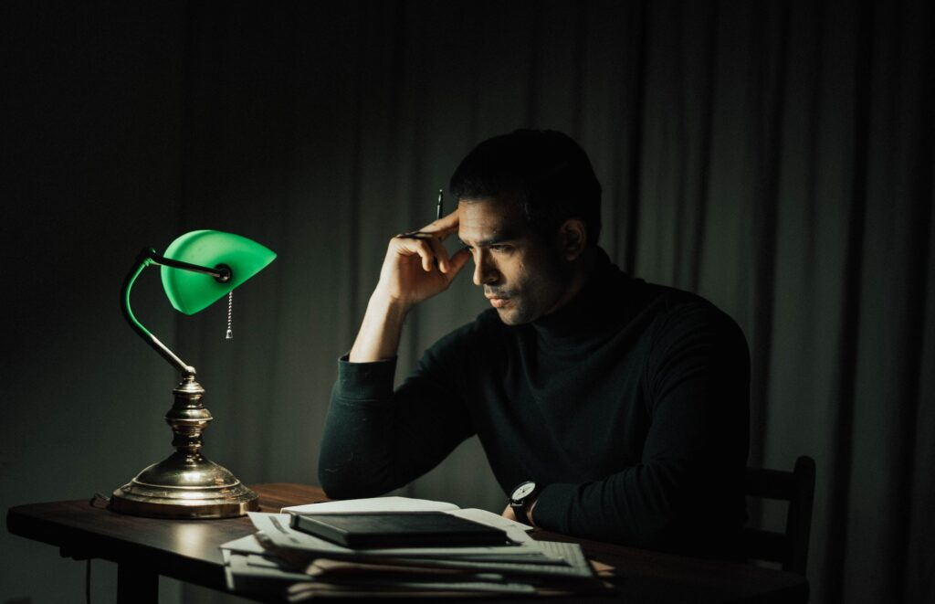 A man deep in thought while sitting at a desk with his hand on his forehead