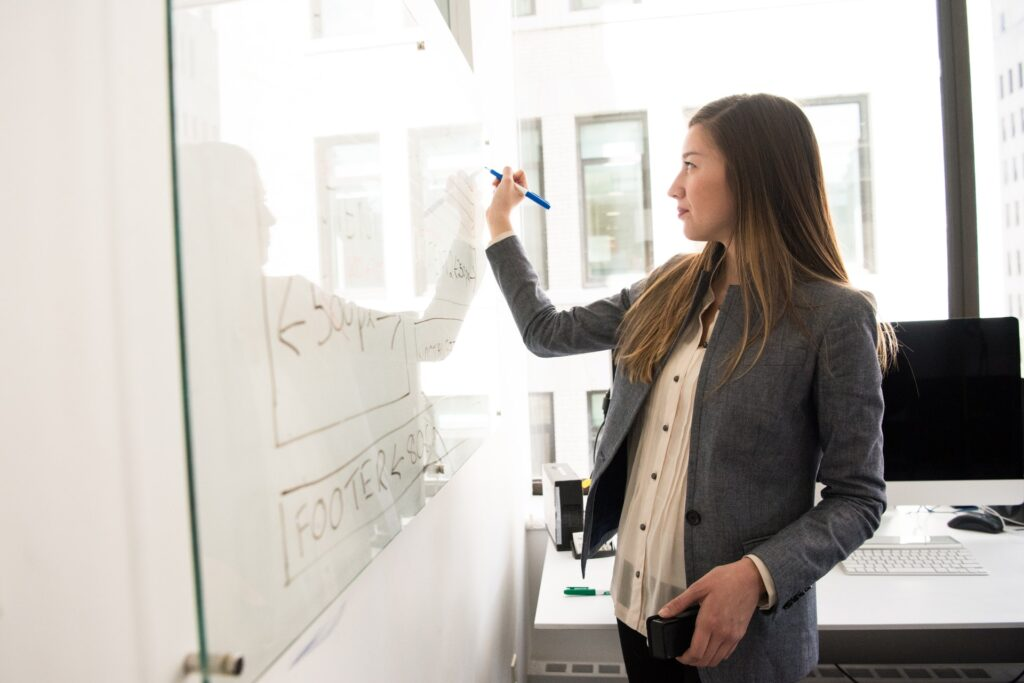 A woman in a gray blazer writing something on a white board